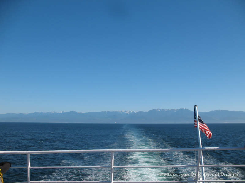 View of Salish Sea looking out the back of the Black Ball Ferry, mountains in the background