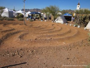 Sundial in the sand with craft vendor tents in background, Superstition Mountain Museum