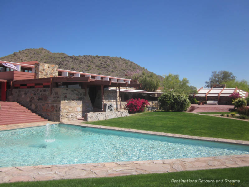 Pool and yard in front of Taliesin West house with mountain in background