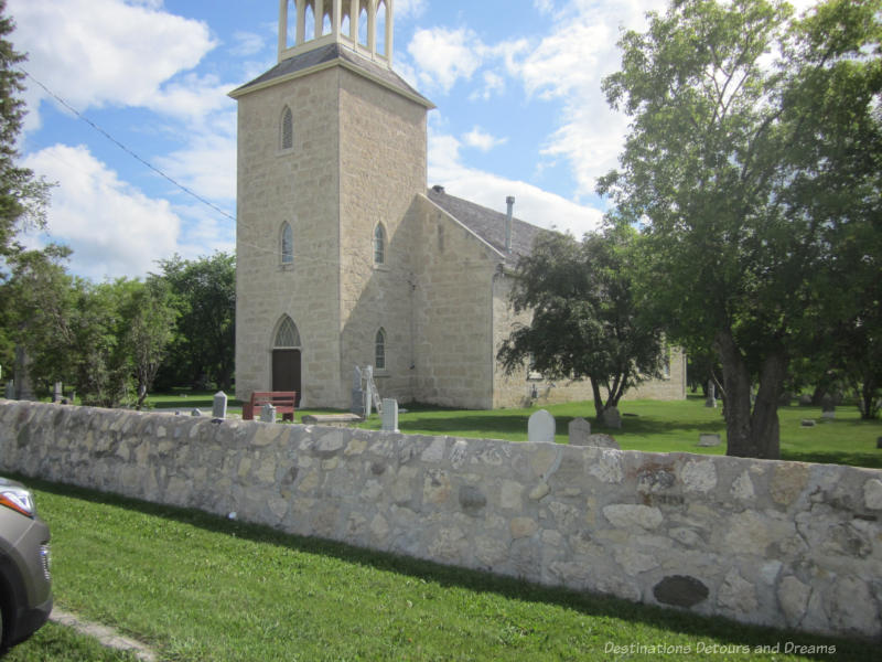Stone church surrounded by cemetery and a low stone wall