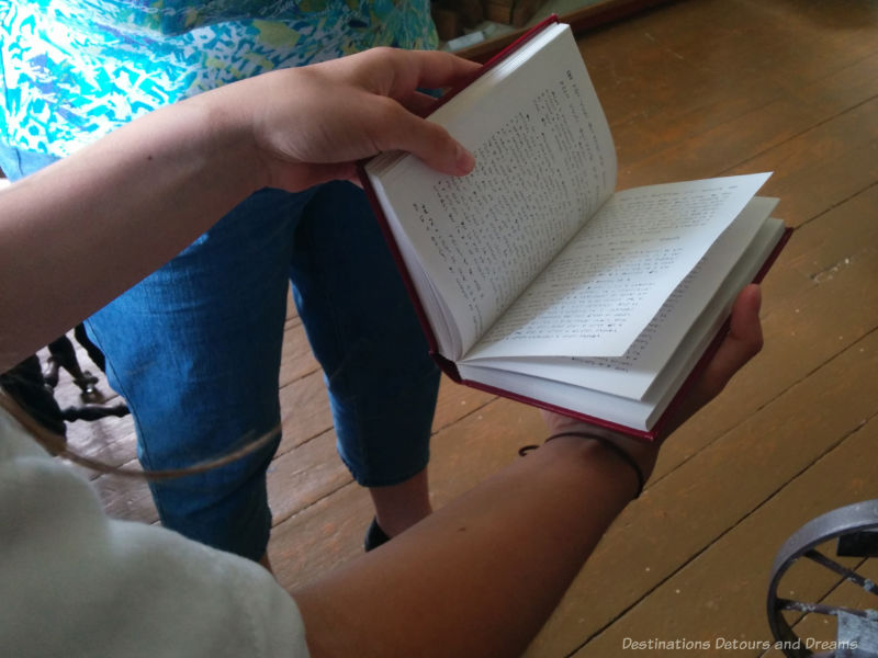 Hand holding a Cree prayer book at St Andrew's Rectory in Manitoba