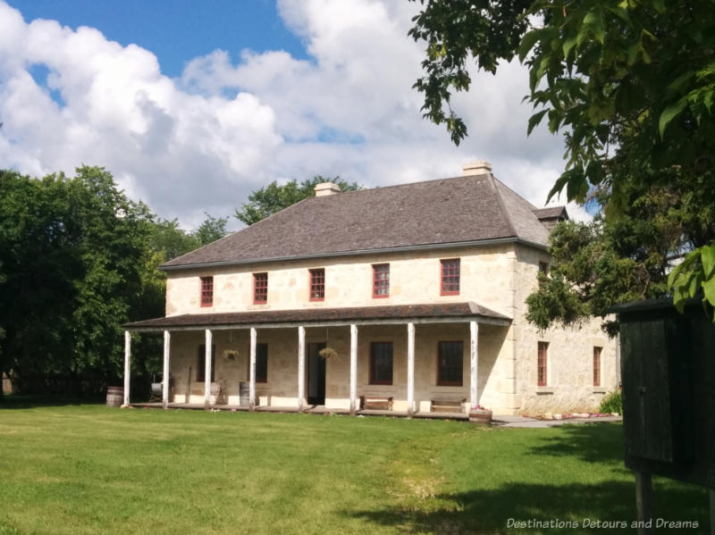 Limestone two story 1800s house with covered front porch - rectory in Manitoba