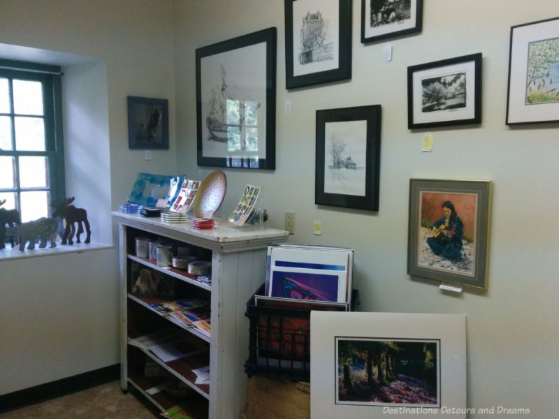 Gift shop with paintings, carvings, glassware, and books on display