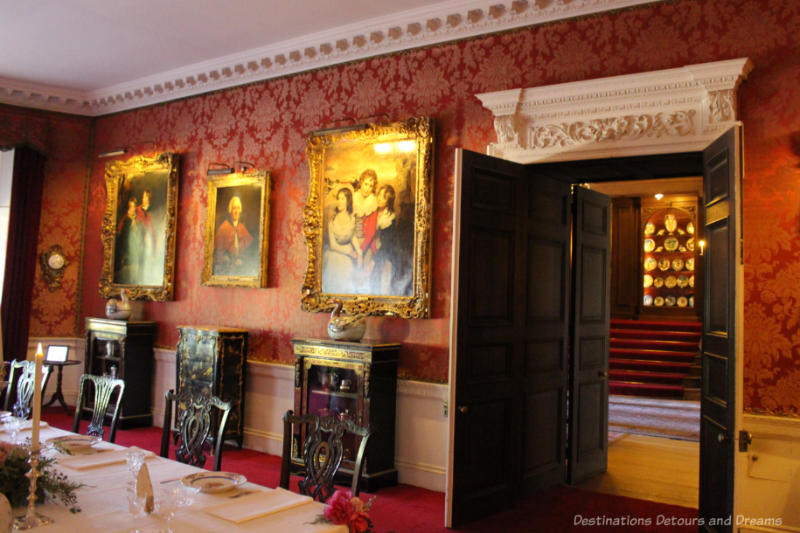 Polesden Lacy dining room with art hanging on red patterned wallpapered walls