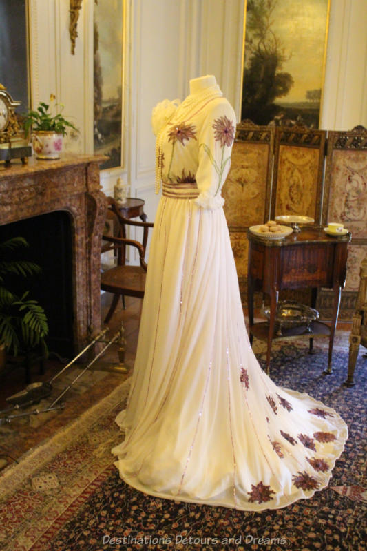 Mannequin in front of fireplace wearing long white flowing gown with embroidered flowers on bodice and train