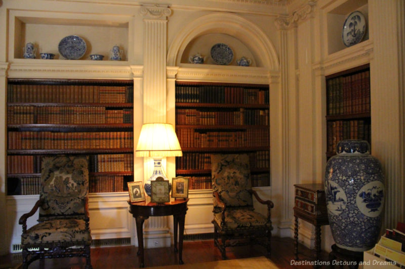 Shelves containing books recessed in white walls with ornate upholstered chairs in front