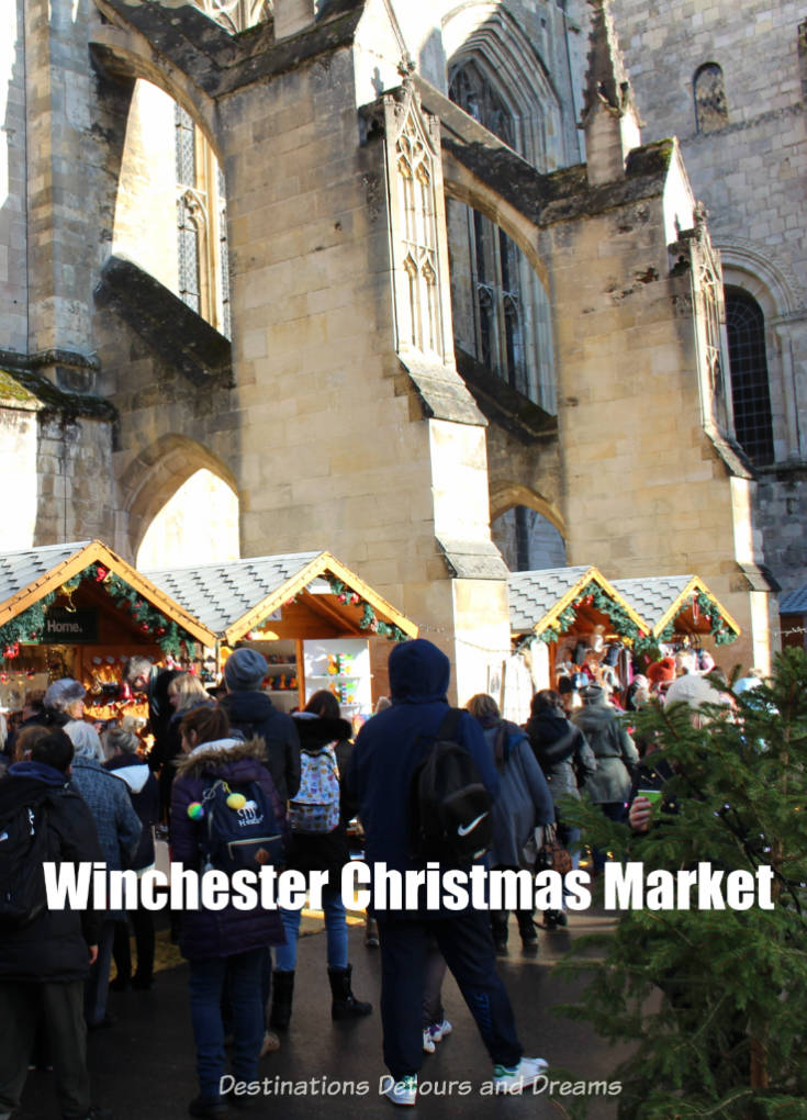 Wooden stalls at Winchester Christmas Market with Winchester Cathedral wall in background