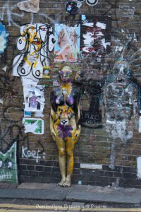 London street art in Brick Lane: work of several artists on Buxton Street building wall includes a three-dimension female body protruding from wall