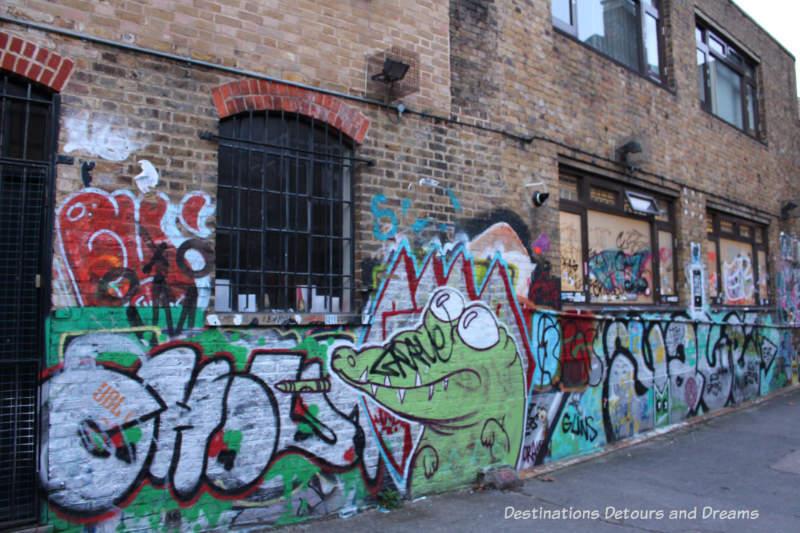 London street art in Brick Lane: graffiti-like drawing in the aley leading to Seven Stars car park