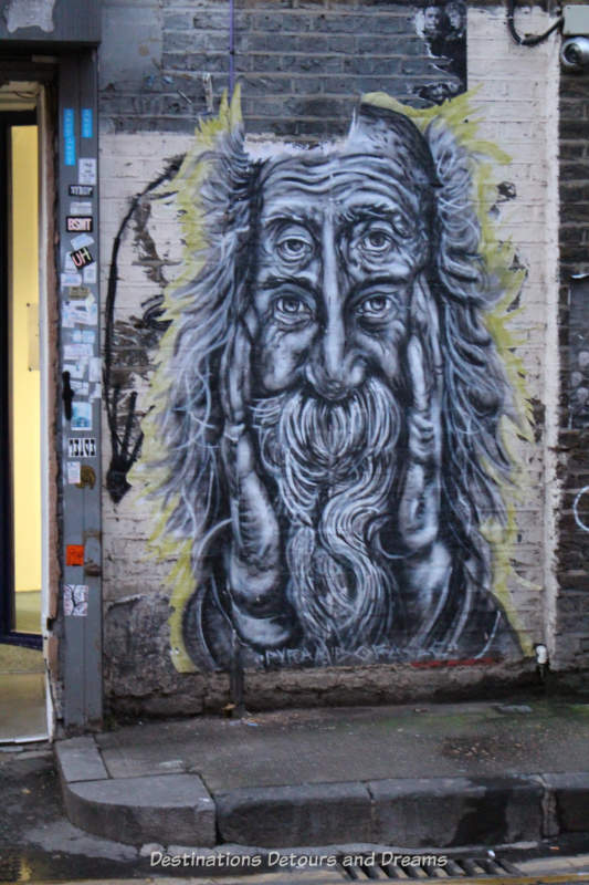 London street art in Brick Lane: monochrome paste-up of an old man by U.S. artist Pyramid Oracle