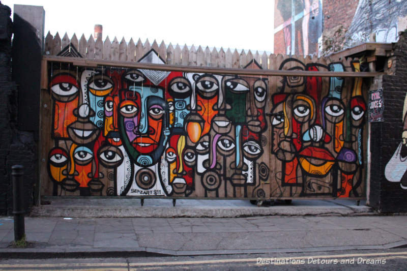 London street art in Brick Lane: painting of African masks by Senzart 911 (Senzo Nhlap) from Soweto,South Africa