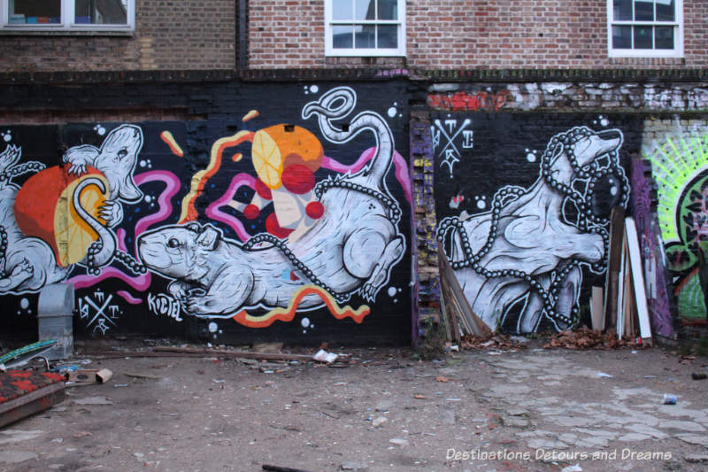 London street art in Brick Lane; rats and oranges, a collaboration between artists ThisOne and Koctel in the Seven Stars Car Park