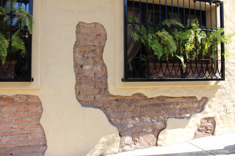 The Colourful Architecture and History of Gringo Gulch, Puerto Vallarta, Mexico: Part of old stone wall left unplastered to reveal brick behind