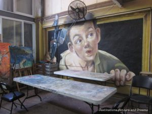 Mural by Adrian Takano of a boy holding paint brushes and coming out of a frame