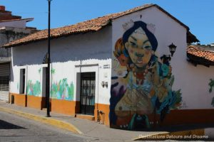 Puerto Vallarta street art: woman with outstretched folded hands, part of Restore Coral Mural project