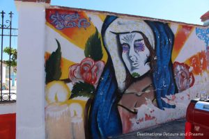 Mural of a woman and candles on the wall of El Panteón Cemetery in Puerto Vallarta