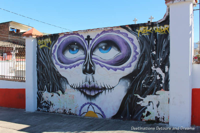 Mural of woman with purple-ringed eyes on the wall of El Panteón Cemetery in Puerto Vallarta