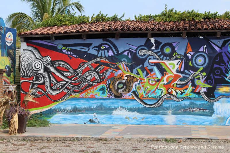 Puerto Vallarta street art: stylized picture of the sea with geometric shapes and octopus with arms reaching through the painting