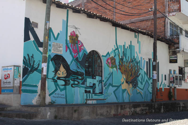 Puerto Vallart street art: two human heads and two sad fish submerged in a geometric sea of turquoise and blue