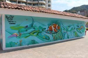 Puerto Vallarta street art: large brown fish trapped in white plastic in the middle of a large turquoise see with reefs