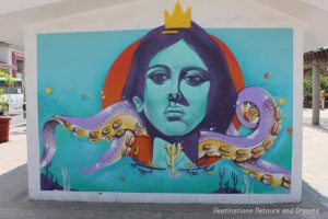 Puerto Vallarta street art: human face with serious expression wearing gold crown and being choked by purple octopus arms
