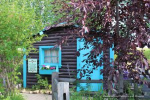 Turquoise trimmed log cabin, once a motel unit, in Pioneer Park in Fairbanks, Alaska