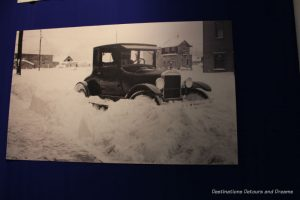 Vintage photo of car stuck in snow at Fountainhead Antique Auto Museum