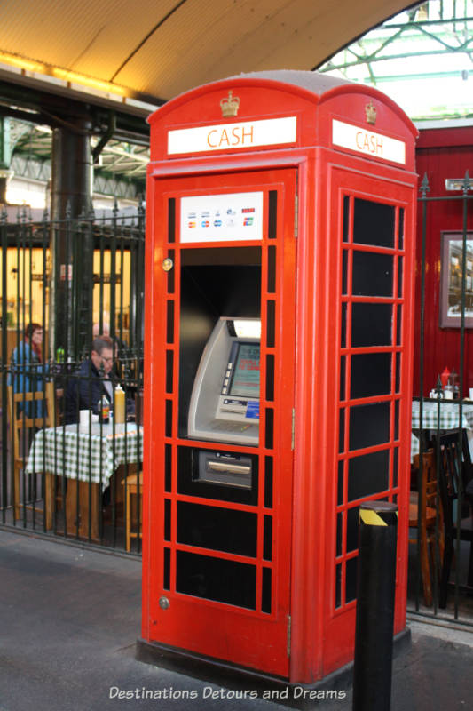Red phone booth used as an ATM station in Borough Market