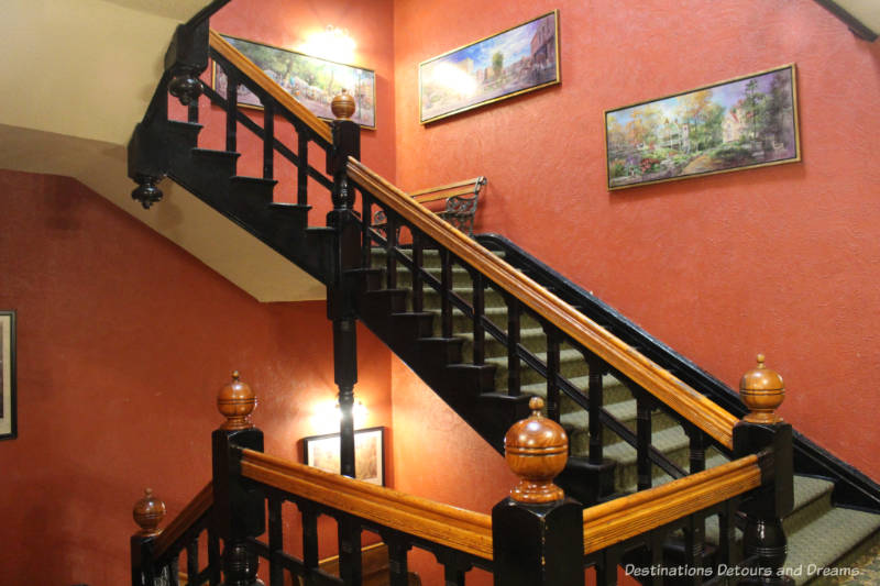 Stairwell with wood-trimmed staircase on art on red coloured walls at Crescent Hotel