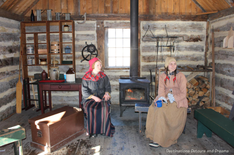 Costumed interpreters inside a cabin at Fort Gibraltar