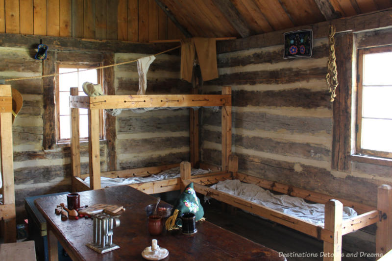Crude wood cots and a table with games in the voyageur winter cabin at Fort Gibraltar in Winnipeg, Manitoba