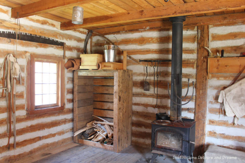 Wood stove, wood stack and items hung on walls in workshop at Fort Gibraltar in Winnipeg, Manitoba