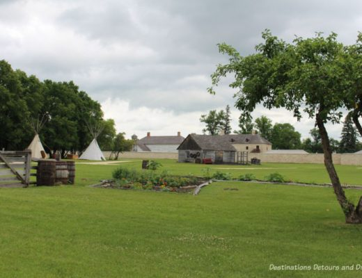 View of field and stone wall and buildings of Lower Fort Garry