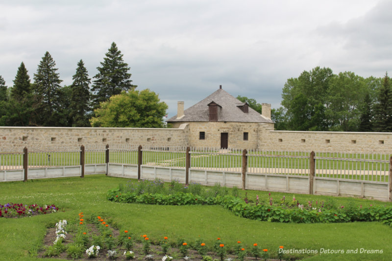 Two sides of the stone wall around Lower Fort Garry with a circular stone bastion at the corner