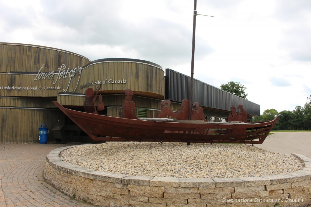 York boat sculpture in front of the flowing lines of the Interpretative Centre of Lower Fort Garry