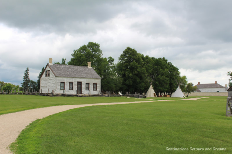 Wooden farm manager's cottage beside tepees on field outside Lower Fort Garry