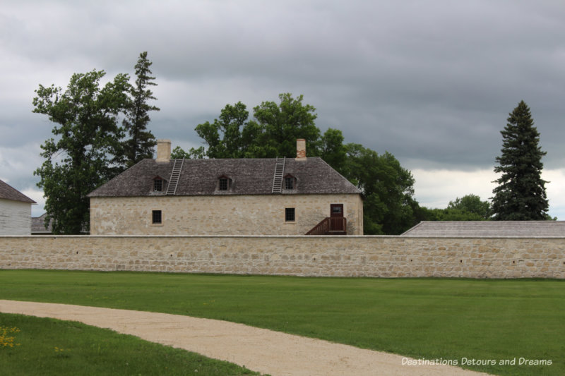 Stone wall of Lower Fort Garry with stone building behind it