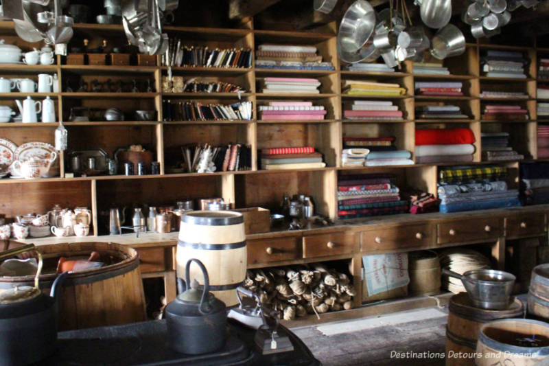 Shelves of clothes, housewares and books and hanging pots in the store at Lower Fort Garry National Historic Site