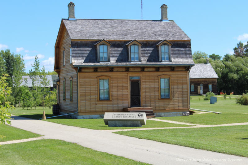 Gambrel-roofed Bohemier house with Turrene log house in background at St. Norbert Provincial Heritage Park, Manitoba