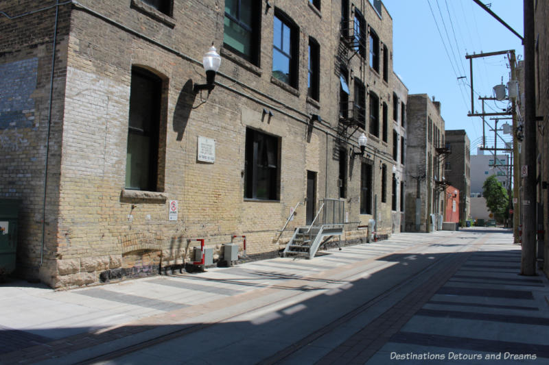 Winnipeg alleyway with railway spur lines and old warehouse loading docks reminds us of Hell's Alley
