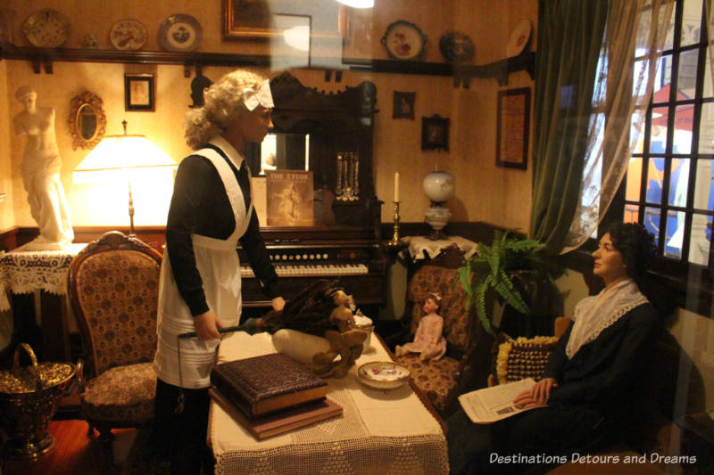 Woman and her maid mannequins inside a 1919 drawing room at the Manitoba Museum Urban Gallery