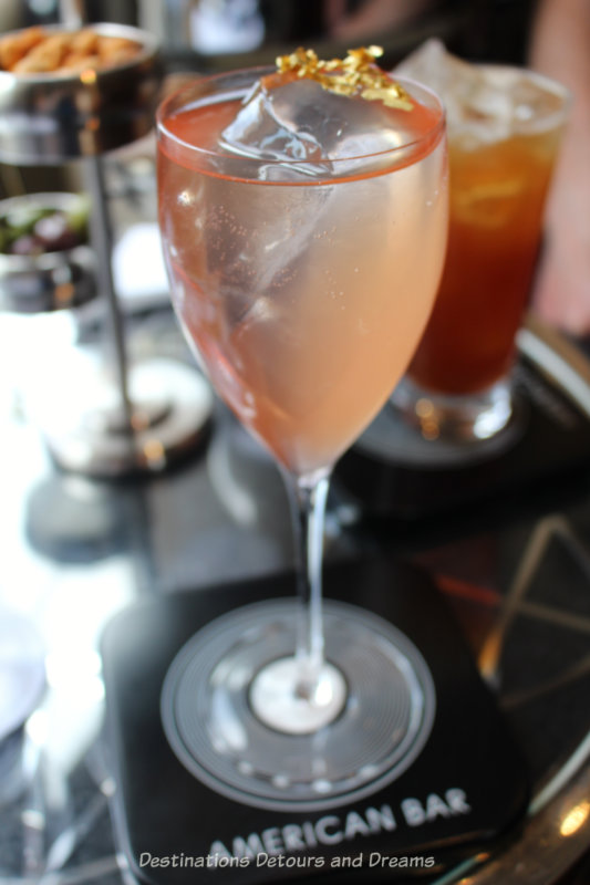 Peach-rose coloured cocktail with gold leaf floating on it at the London Savoy Hotel American Bar