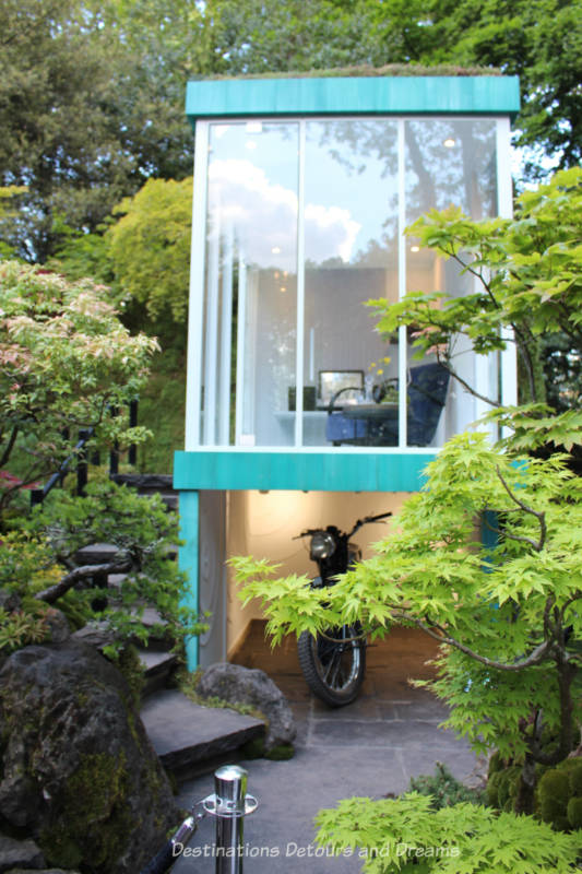 Two storey building with glass-walled tea house on upper level and parking space below in the Green Switch at the 2019 Chelsea Flower Show