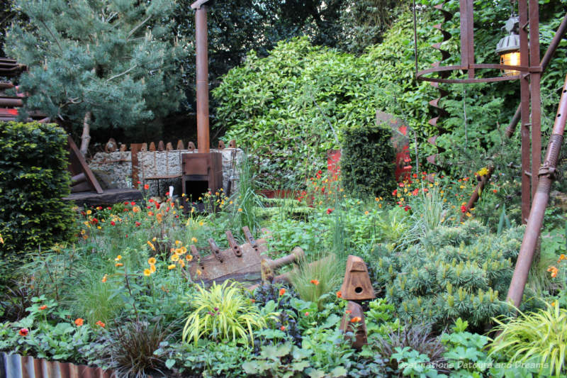 Rusting industrial pieces amid a lush naturalistic garden in the Forgotten Quarry Garden at the 2019 Chelsea Flower Show