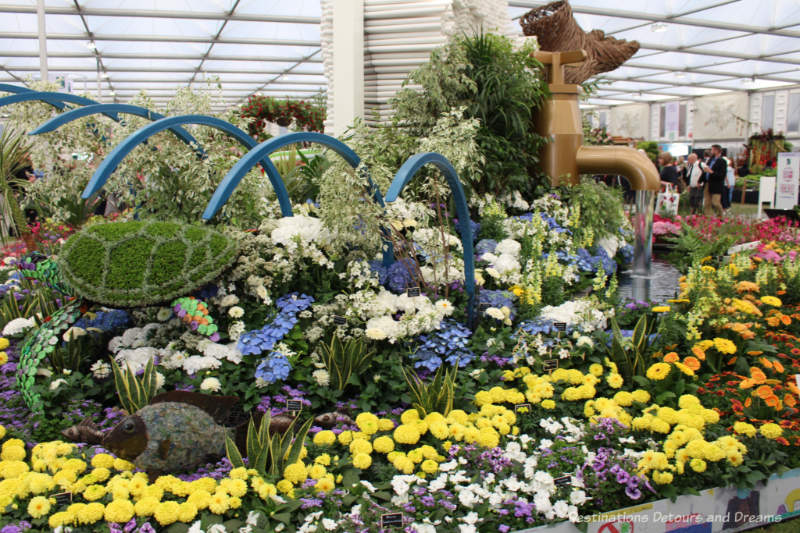 Blue and yellow flowers, blue archway, bronze water pipe, and stream - part of the Floella's Future exhibit at the 2019 Chelsea Flower Show
