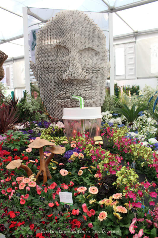 Giant face made out of straws in the Floella's Future display at the 2019 Chelsea Flower Show
