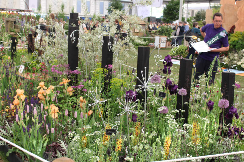 A naturalistic planting of gold and purple flowers with silver garden ornaments at the 2019 Chelsea Flower Show