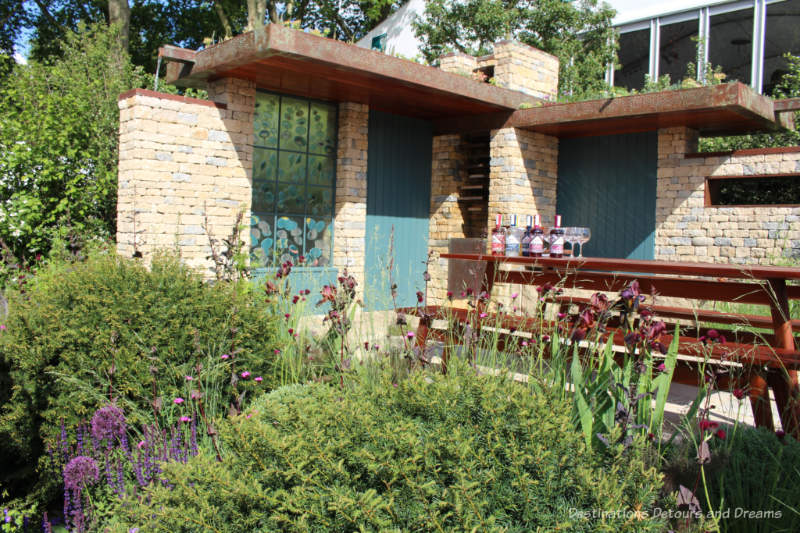 Courtyard with picnic table in a pastoral setting in the Warner's Distillery Garden at the 2019 Chelsea Flower Show