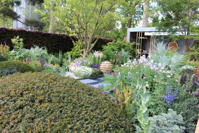 Topiary domes, colourful plants, and a relaxation space in the Morgan Stanley Garden at the 2019 Chelsea Flower Show
