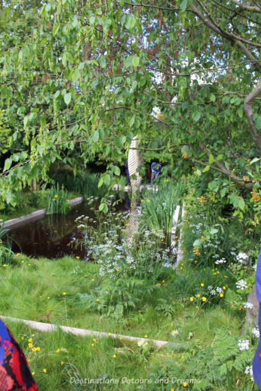 Pond with bronze sculpture in it surrounded by woodland at the Chelsea 2019 Savills and David Harber Show Garden